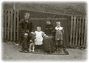Family of four by fence with dog